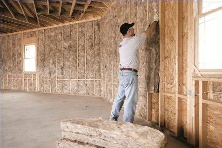 Ocieplanie ściany szkieletowej budynku wełną mineralną.