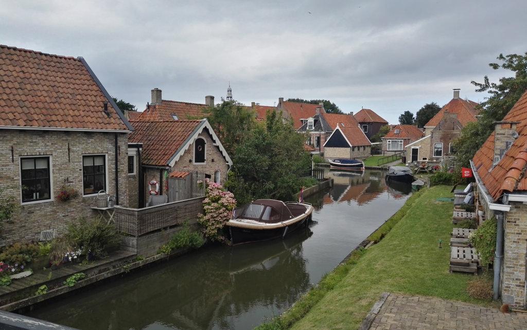 Urokliwe ceglane domki z ceramiczną dachówką nad kanałem w jednym z holenderskich miasteczek.