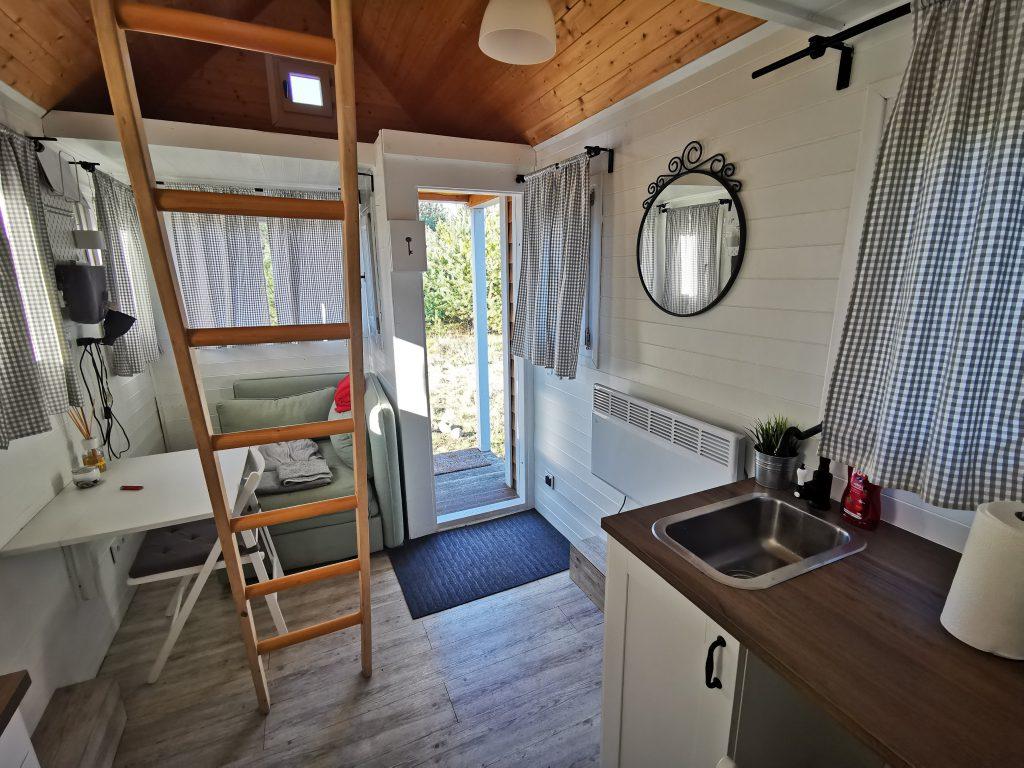 Wnętrze Tiny House. Widoczne są drzwi wejściowe, fotel, stolik i krzesło, zasłonki w oknach, lustro, grzejnik elektryczny, mały zlew i szafka kuchenna oraz drabina do sypialni.