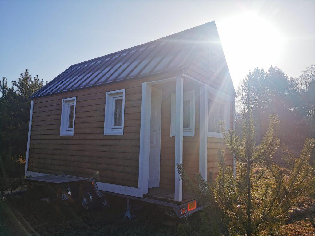 Tiny House w Mental Shelter widziany z zewnątrz. Obity drewnem, z blaszanym dachem, widocznych jest kilka okien i drzwi wejściowe.